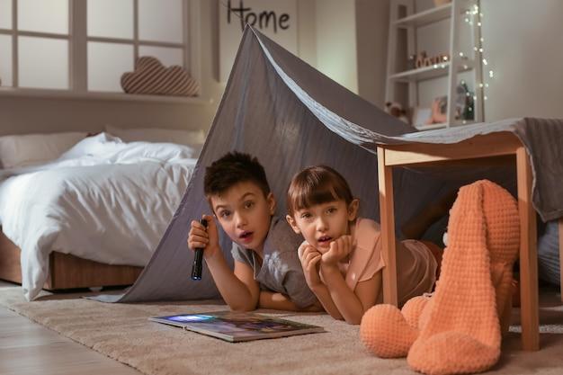 Испуганные маленькие дети читают сказку на ночь дома