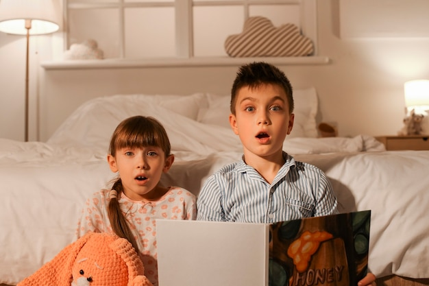 Scared little children reading bedtime story at home