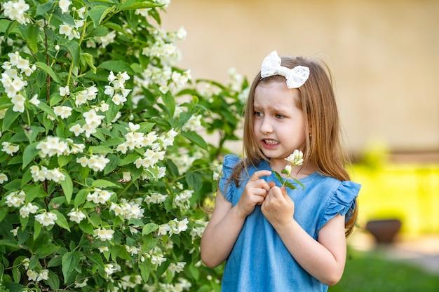 Испуганная маленькая девочка возле куста жасмина