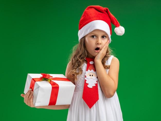 Bambina spaventata che indossa cappello di natale con cravatta che tiene scatola regalo mettendo la mano sulla guancia isolata sul muro verde
