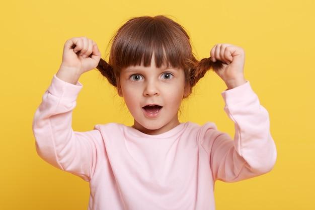 옅은 분홍색 셔츠를 입고 겁 먹은 어린 소녀가 땋은 머리를 잡아 당기고 큰 눈과 크게 벌린 입으로 카메라를 직접 바라보며 두려움과 충격을 표현하고 무언가를 두려워합니다.