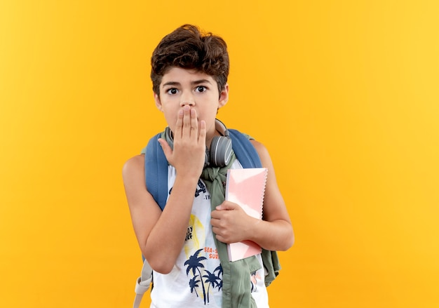 ノートブックを保持し、黄色で隔離の手で口を覆ったバックバッグとヘッドフォンを身に着けている怖い小さな男子生徒