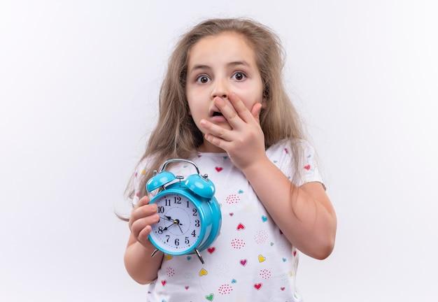 알람 시계를 들고 흰색 티셔츠를 입고 무서워 어린 학교 소녀 격리 된 흰색 배경에 입 덮여