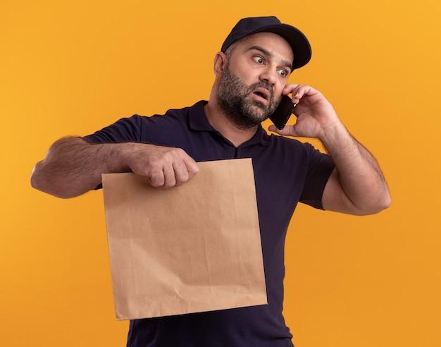 노란색 벽에 고립 된 전화에 유니폼과 모자를 들고 종이 음식 패키지를 들고 측면 중년 배달 남자를보고 무서워
