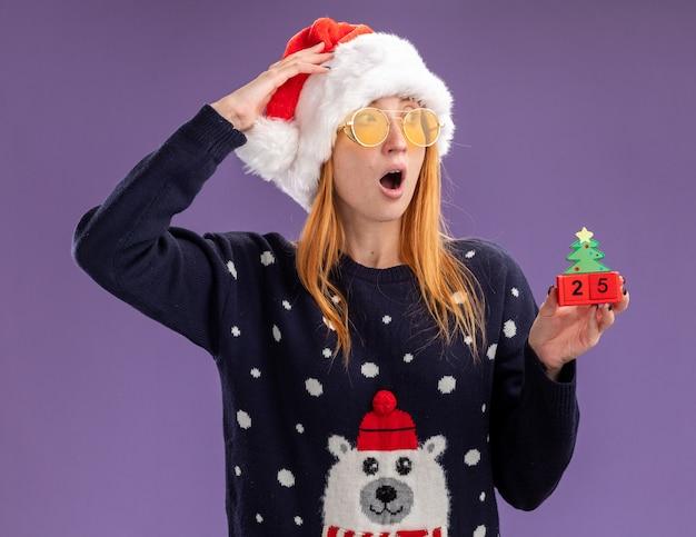 紫色の背景で隔離の額に手を置いてクリスマスのおもちゃを保持しているメガネとクリスマスセーターと帽子を身に着けている側の若い美しい少女を見て怖い