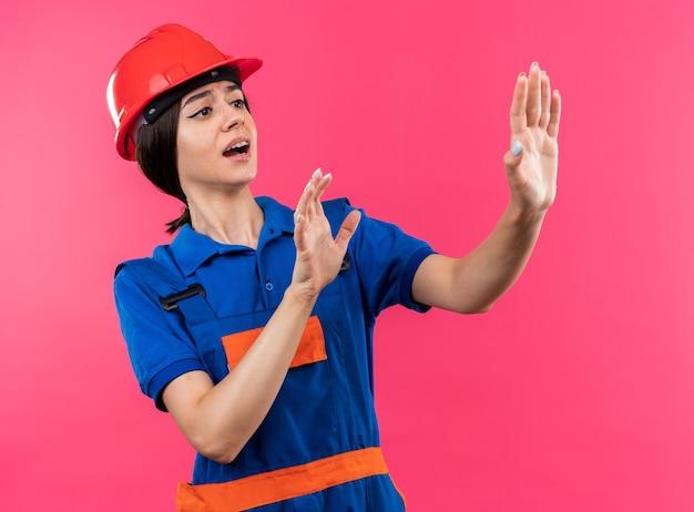 Испуганный, глядя в сторону, молодая женщина-строитель в униформе, протягивая руки сбоку