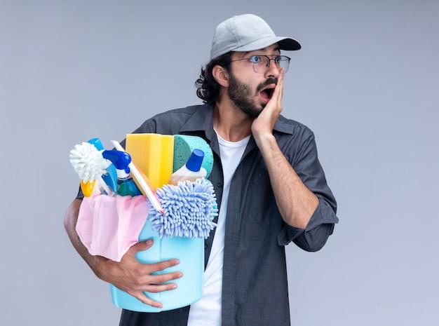 白い壁に隔離された頬に手を置くクリーニングツールのバケツを保持しているtシャツとキャップを身に着けている若いハンサムなクリーニング男を見て怖い