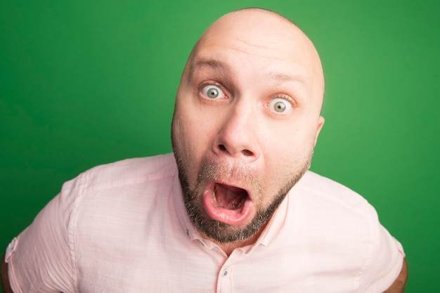 Uomo calvo di mezza età spaventato che indossa la maglietta rosa