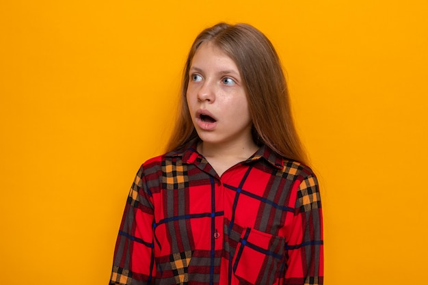 オレンジ色の壁に分離された赤いシャツを着て怖い顔の美しい少女