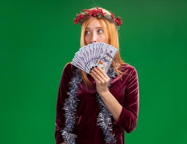 緑の背景に分離された現金で首に花輪と花輪で覆われた顔に赤いドレスを着て怖い顔の若い美しい少女