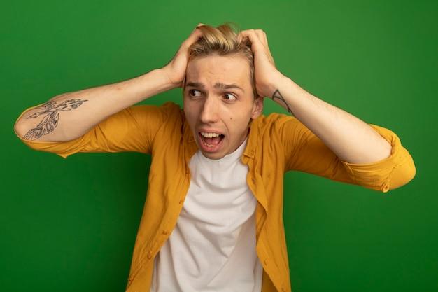 Spaventato guardando al lato giovane ragazzo biondo che indossa la maglietta gialla ha afferrato la testa isolata sul verde