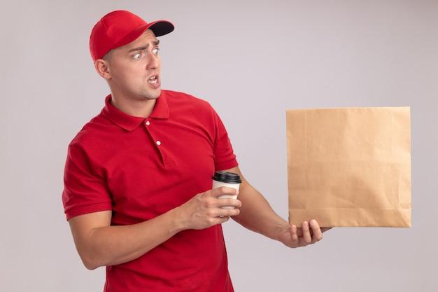Spaventato guardando al lato giovane uomo di consegna che indossa l'uniforme con il cappuccio che tiene il pacchetto di cibo di carta con una tazza di caffè isolato sulla parete bianca