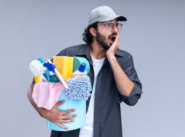 Spaventato guardando al lato giovane bel ragazzo delle pulizie che indossa t-shirt e berretto che tiene secchio di strumenti di pulizia mettendo la mano sulla guancia isolata sul muro bianco