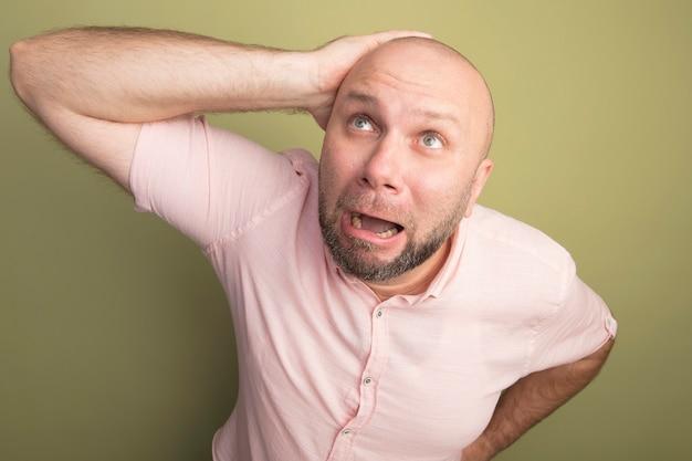 Spaventato alzando lo sguardo uomo calvo di mezza età che indossa la maglietta rosa mettendo la mano sulla testa isolata su verde oliva