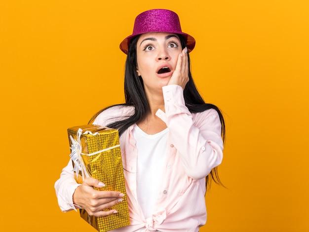 オレンジ色の壁に隔離された手でギフトボックスで覆われた頬を保持しているパーティーハットを身に着けている若い美しい少女を見上げるのが怖い