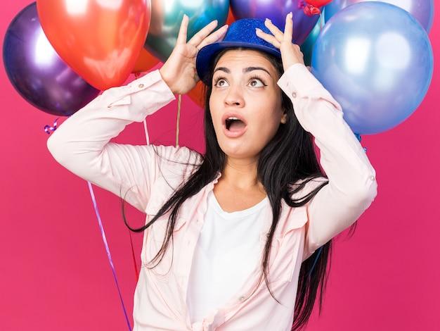前の風船に立っているパーティーハットをかぶっている若い美しい女の子を見上げるのが怖い