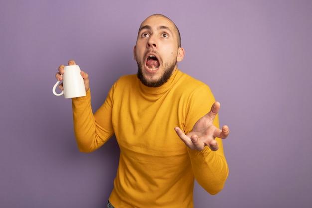보라색에 고립 된 손을 확산 아래로 컵을 들고 젊은 잘 생긴 남자를 찾고 무서 워