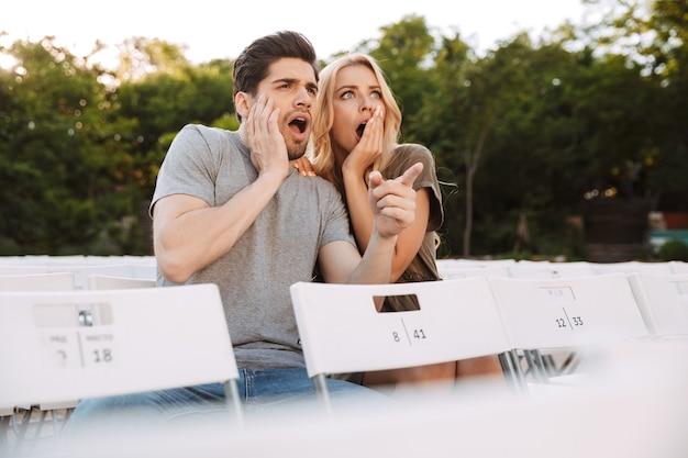 Испуганная милая молодая пара вместе сидят на стульях и смотрят фильм на открытом воздухе