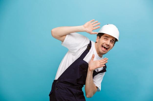 Испуганный мужчина-строитель в защитном шлеме, прикрывшись криком и глядя в сторону через синюю стену