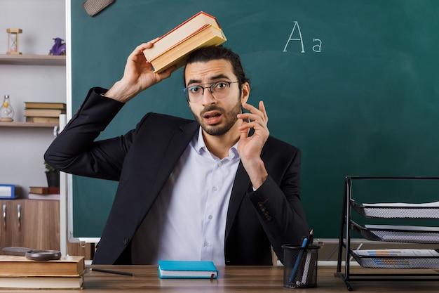 Insegnante maschio spaventato con gli occhiali che tiene un libro sulla testa seduto a tavola con gli strumenti della scuola in aula