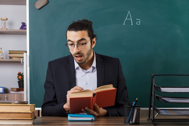Insegnante maschio spaventato con gli occhiali che tiene e legge un libro seduto al tavolo con gli strumenti della scuola in classe