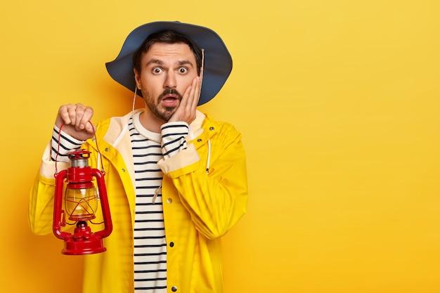 Scared male traveler holds little red lantern for lightening in darkness, keeps palm on cheek, wears waterproof yellow raincoat