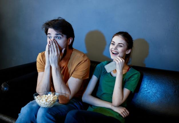 Испуганный мужчина и счастливая женщина смотрят телевизор вечером на диване