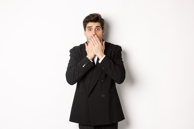 Scared man in formal suit, gasping and looking frightened at camera, standing against white background