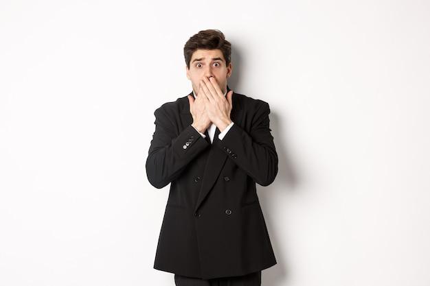 Uomo spaventato in abito formale, ansimando e guardando spaventato la telecamera, in piedi su sfondo bianco