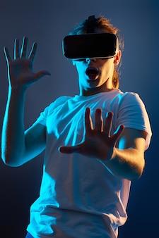 紺色の背景でビデオゲームをプレイする仮想現実のメガネで怖い男。ネオンライト。