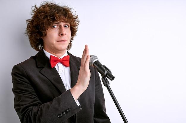 Испуганный мужчина на сцене с микрофоном, кудрявый мужчина боится публичных выступлений. изолированные на белом