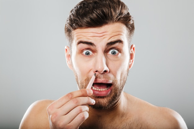 Scared man removing nose hair with tweezers