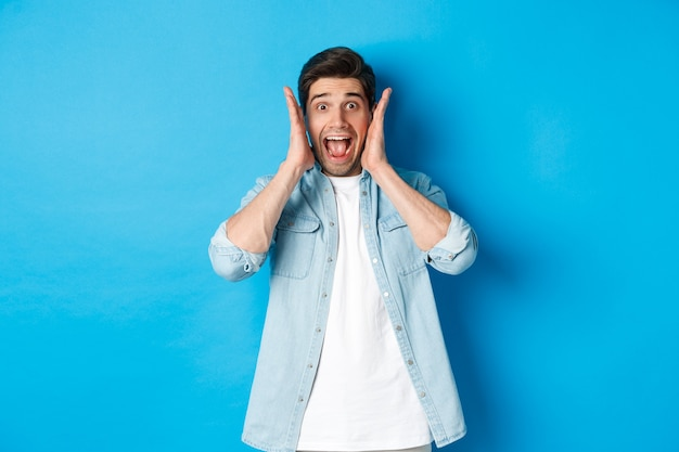 Scared man screaming and looking startled at something, standing against blue background.