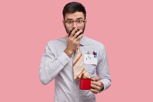 Insegnante uomo spaventato copre la bocca, ha un'espressione sorpresa, vestito con abiti formali