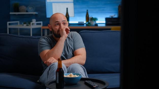 Испуганный мужчина смотрит фильм ужасов по телевизору и ест попкорн, сидя на диване