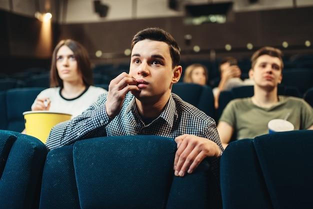 Испуганный человек смотрит фильм в кино