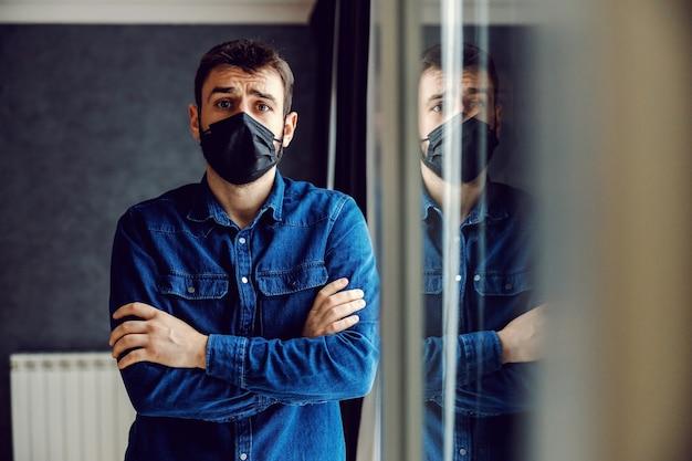 코로나 바이러스 봉쇄 기간 동안 무기를 들고 창 옆에 마스크 서있는 무서워하는 남자