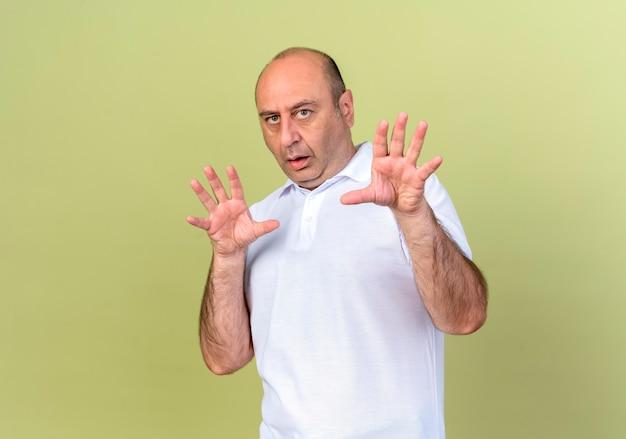 Uomo maturo spaventato che si tiene per mano intorno al fronte isolato sulla parete verde oliva