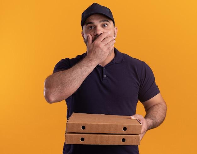 유니폼과 모자를 들고 무서워 중년 배달 남자가 피자 상자를 들고 노란색 벽에 고립 된 손으로 입을 덮여