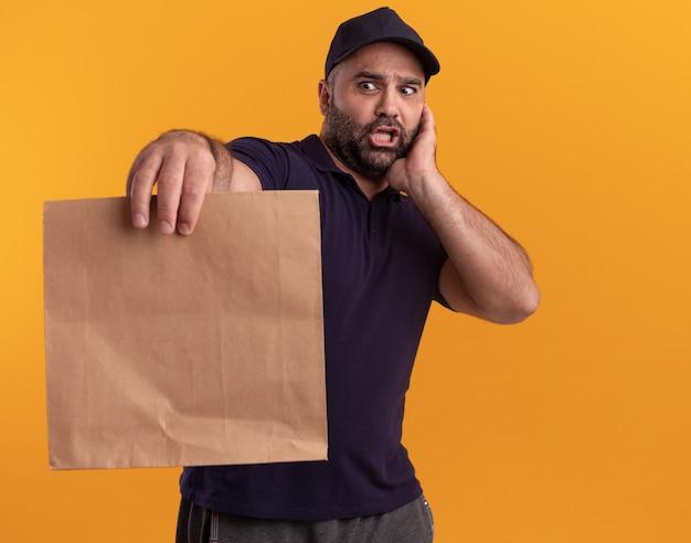 Uomo di consegna di mezza età spaventato in uniforme e cappuccio che tiene fuori il pacchetto di cibo di carta isolato sulla parete gialla