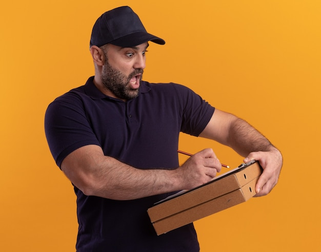 Scared middle-aged delivery man in uniform and cap writing something on clipboard on pizza boxes isolated on yellow wall