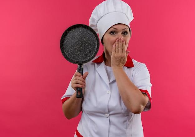 Il cuoco femminile di mezza età spaventato in uniforme del cuoco unico che tiene la padella ha coperto la bocca con la mano con lo spazio della copia