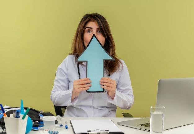 聴診器を備えた医療用ローブを身に着けている怖い中年の女性医師が、コピースペース付きの方向マークで顔を覆っている医療ツールを備えたラップトップでデスクワークに座っています