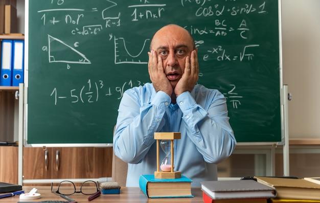 Insegnante maschio di mezza età spaventato si siede a tavola con materiale scolastico volto coperto con le mani in classe