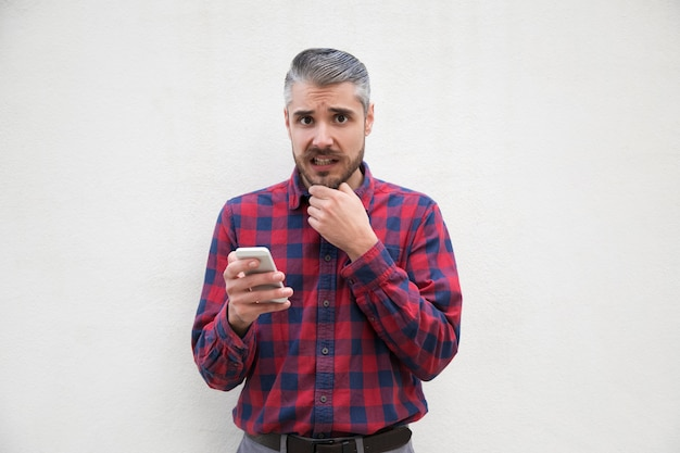 Scared middle aged man holding smartphone