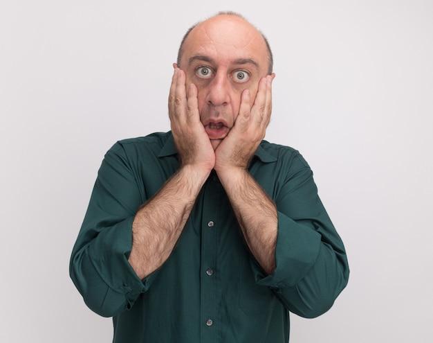 白い壁に隔離された緑のtシャツで覆われた顔を身に着けている怖い中年男性
