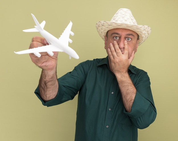 Uomo di mezza età spaventato che indossa t-shirt verde e cappello che tiene aeroplano giocattolo mettendo la mano sulla bocca isolata sulla parete verde oliva