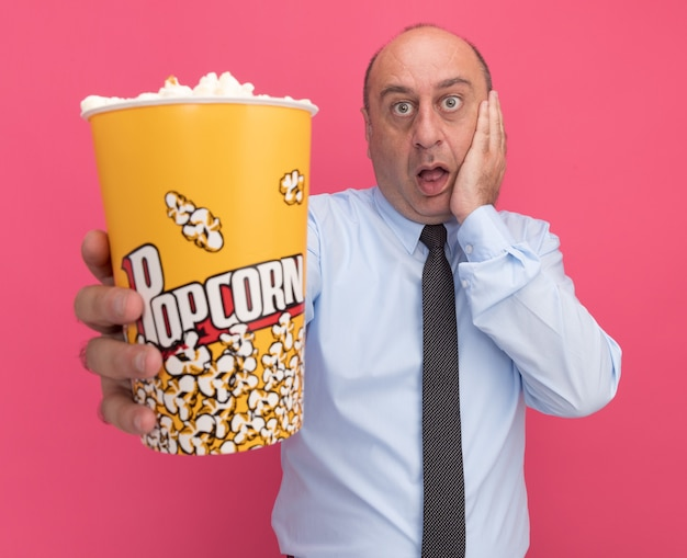 Scared middle-aged man wearing white t-shirt with tie holding out bucket of popcorn at front putting hand on cheek isolated on pink wall
