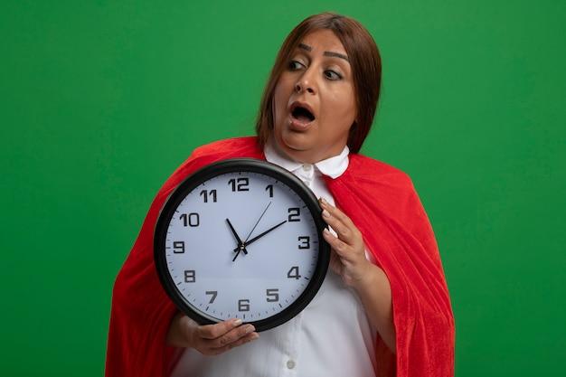 Spaventata donna di mezza età supereroe guardando l'orologio di parete laterale della holding isolato sul verde