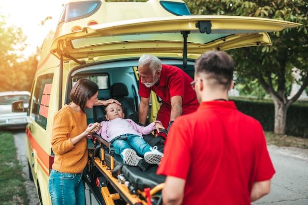 Испуганная мать, стоящая с врачами и ее раненой дочерью.
